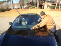 A skilled auto glass repairman replaces the windshield of a vehicle.