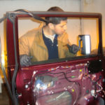 Man replacing auto glass in an antique car