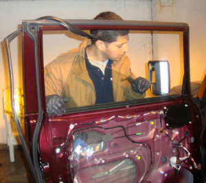 Man replacing antique car's auto glass